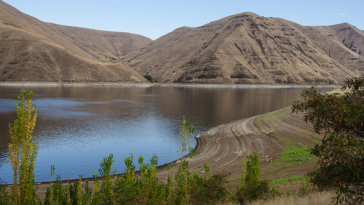 A wide view of Idaho's Hells Canyon reservoir in drought, showing a dry shoreline and receding waterline. 2018 photo.